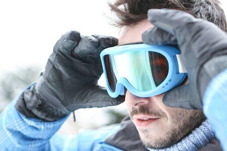 ski goggles: Man on ski trip putting on his ski goggles in winter
