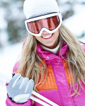 ski goggles: Smiling woman skiing with ski goggles in winter through snow