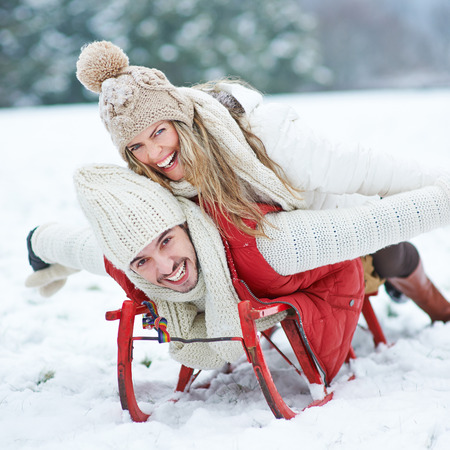 Couple having fun while sledding on sled in winter