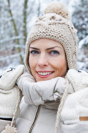 stocking cap: Smiling woman standing with wool cap in winter snow