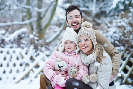 Happy family with daughter smiling together in winter snow