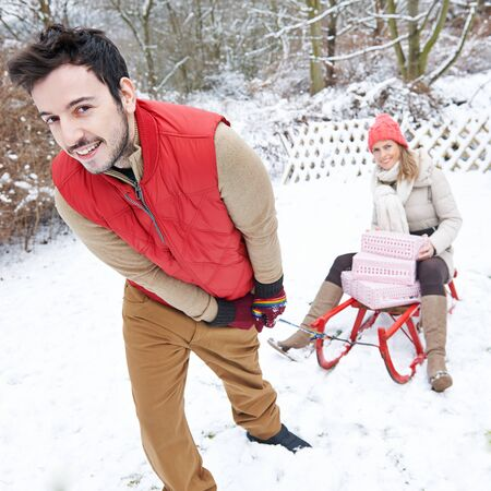 sledging people: Happy couple sledding in winter with sled with christmas gifts