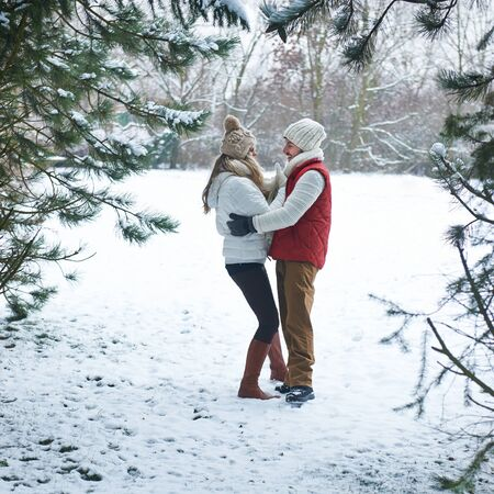 winter couple: Happy couple standing in winter forest with snow