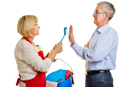 chores: Senior couple with cleaning supplies having discussion over chores Stock Photo