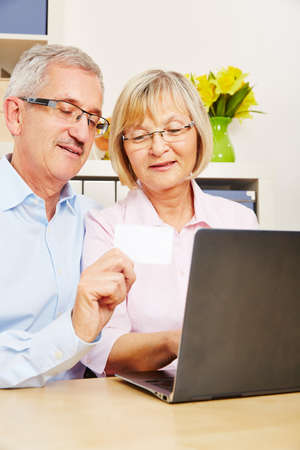 electronically: Senior couple doing online shopping with laptop computer and credit card Stock Photo