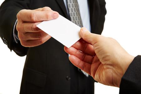 Handen van twee ondernemers geven en nemen een lege visitekaartje