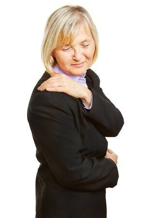 pangs: Old woman in a business suit having shoulder pain and holding her aching spot Stock Photo