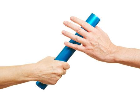 Manos que ofrecen un bastón de relevo azul durante raza running Foto de archivo