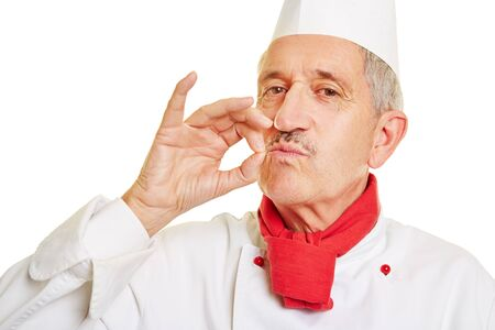 tastes: Happy old chef cook making gesture for good taste with his fingers