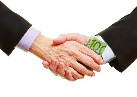 bribery: Hands giving Euro money bill for business bribery during handshake
