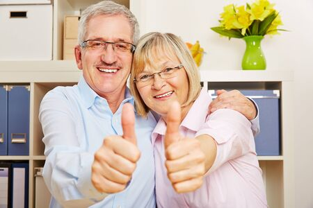 acknowledgment: Happy couple of senior citizens holding thumbs up together