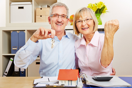 tenant: Happy senior couple cheering together with small house and door keys