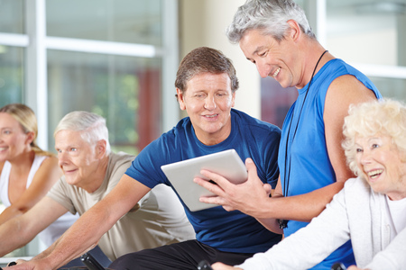 muscle formation: Fitness trainer with tablet computer in gym talking to senior people