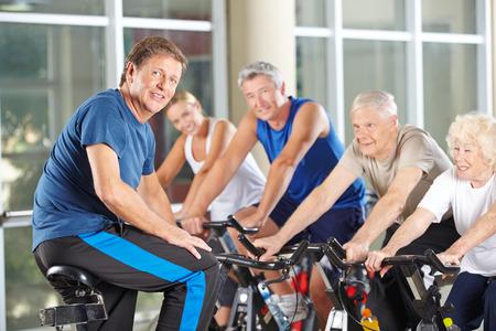 motion: Människan som fitness instruktör i gymmet träna med högre grupp i spinningpass