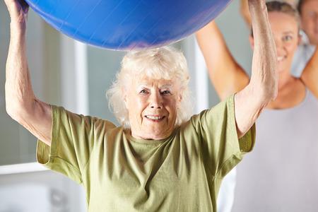 tercera edad: Mujer mayor que ejercita con la bola de la gimnasia en el gimnasio en rehabilitación