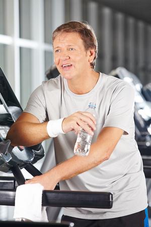 man drinking water: Elderly man drinking water in fitness center on a treadmill