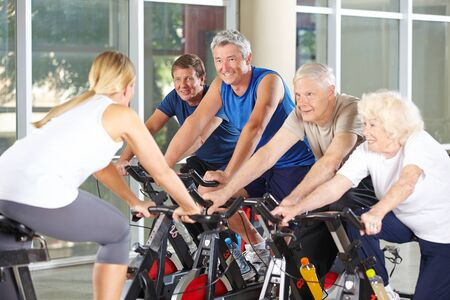 programs: Senior people with trainer in gym exercising on spinning bikes Stock Photo