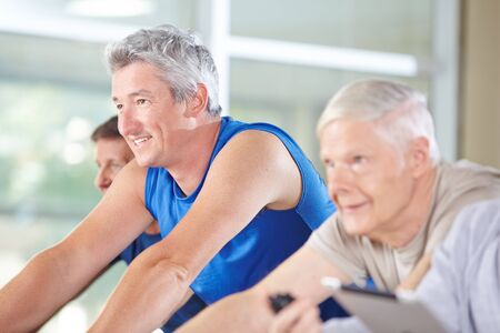 group of men: Three happy senior people riding spinning bikes in gym Stock Photo