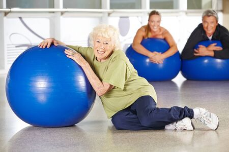 senior exercise: Smiling senior woman sitting with gym ball in a rehab center Stock Photo