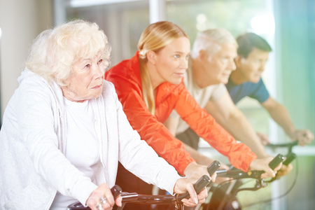 home trainer: Old woman exercising in group on a spinning bike in gym Stock Photo