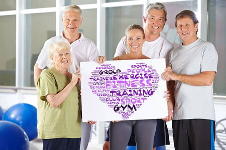 health and fitness: Group of senior people holding fitness concept tag cloud on a cardboard in a gym