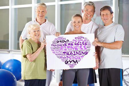 forme et sante: Un groupe de gens supérieurs, détenant concept de remise en forme nuage sur un carton dans un gymnase Banque d'images