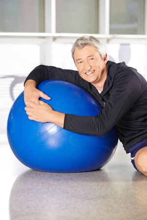gym ball: Happy senior man with gym ball doing back training in fitness center