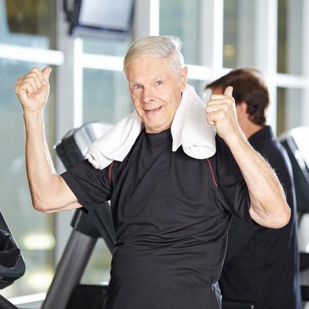 Alter Mann auf dem Laufband im Fitness-Center hält seinen Daumen nach oben Standard-Bild