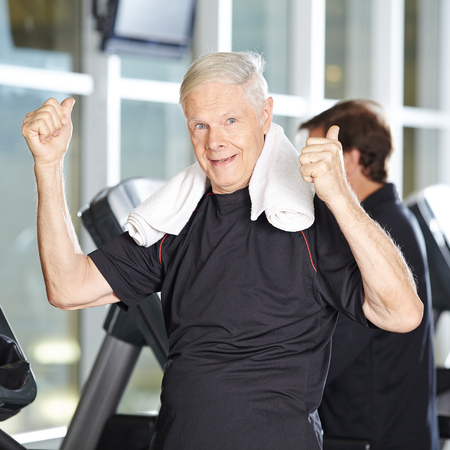 vejez feliz: Viejo hombre en la cinta en el gimnasio celebración de sus pulgares arriba Foto de archivo