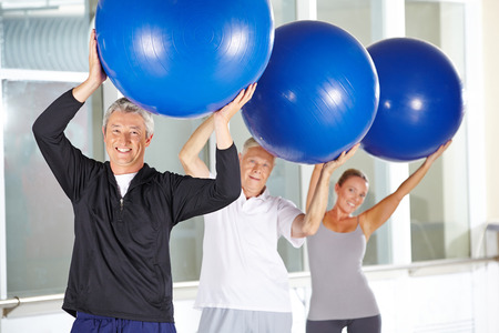 gym ball: Smiling elderly man exercising with gym ball in fitness center during rehab