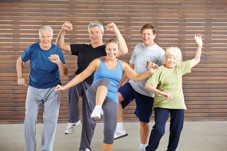 Feliz grupo de personas mayores en la clase Piloxing en un gimnasio