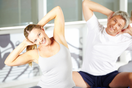 muscle formation: Woman stretching in group in gym during back training Stock Photo