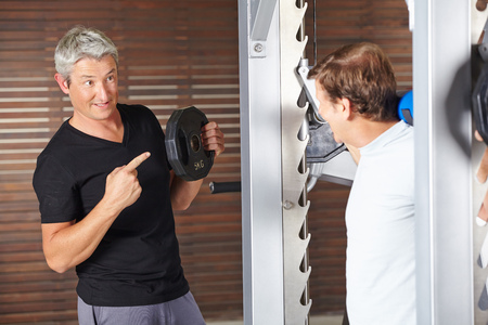 muscle formation: Senior man lifting weights with fitness instructor helping in gym