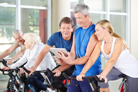 Trainer with tablet PC coaching senior group on spinning bikes in gym