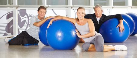 fitness gym: Three smiling senior people with gym balls sitting in a fitness center Stock Photo