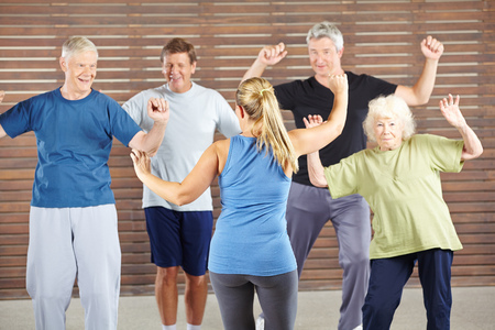 an elderly person: Dancing class with happy senior people in a gym Stock Photo