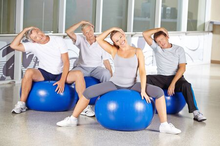 muscle tension: Senior people doing exercises against nape tension in a gym Stock Photo