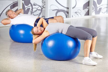 situps: Man and woman exercising in gym on fitness balls