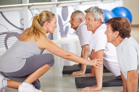 Instructor de la aptitud ayudar a las personas mayores en el gimnasio durante la clase de entrenamiento de la espalda