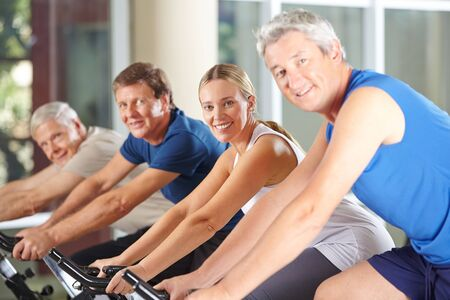 home trainer: Group of happy seniors on spinning bikes in gym Stock Photo