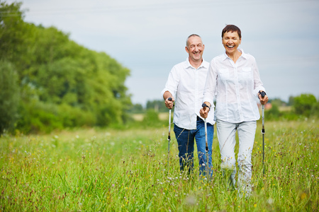 old couple walking: Man and woman hiking in summer over a meadow with walking sticks