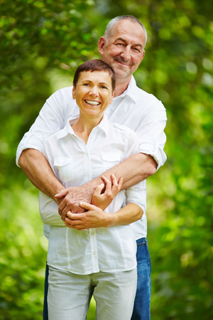senior citizens: Happy senior couple standing together in nature