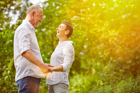 Senior couple laughing together in summer in a forest