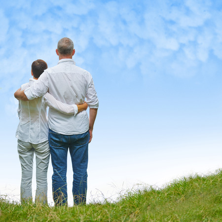 Senior couple looking into blue sky in a green hill