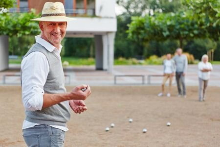 senior men: Smiling old man with ball for boule game in a city Stock Photo