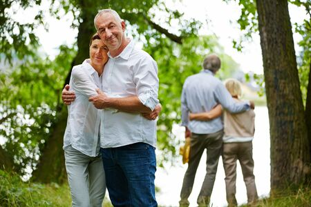 bejaardenhuis: Two happy senior couples embracing in garden of retirement home Stockfoto