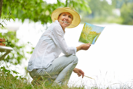 brush in: Old happy woman painting a picture with brush in nature Stock Photo