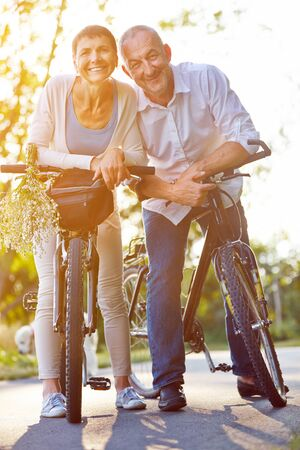 Happy senior couple with bikes on a bike path in summer
