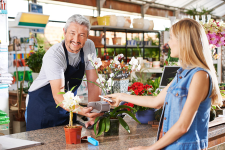 Mobile payment in garden center with salesman and customer