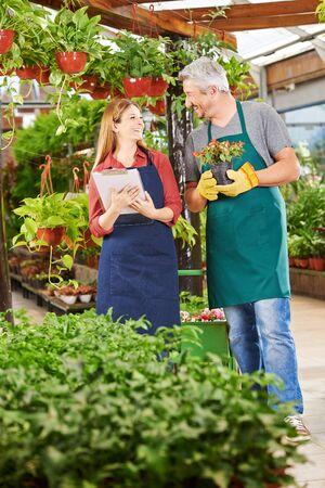 empleados trabajando: Dos empleados felices trabajando juntos en una tienda de guardería